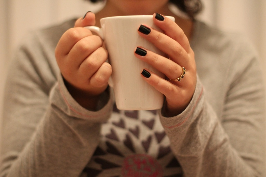 Image shows a woman's hands wrapped around a coffee cup; her nails are painted black and she has a gold ring on.